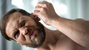 Mann tropft Ohrentropfen ins Ohr