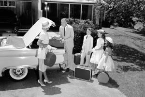 Schwarz-weiß-Foto einer Familie in den 50er Jahren vor einem Auto stehend zur Reise bereit