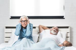 Frau hält sich Ohren zu, weil Mann schnarcht