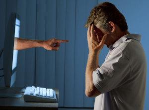 Mann hat Angst vor einer Hand, die aus dem PC kommt