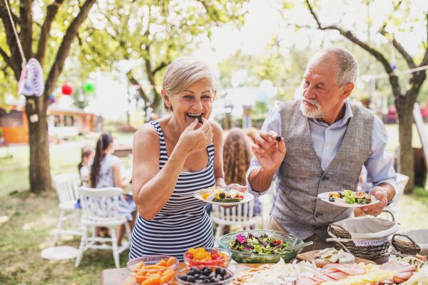 Älteres Paar am Buffet eines Gartenfestes