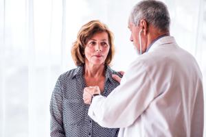 Frau wird beim Arzt abgehört