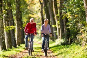 Älteres Paar fährt Fahrrad auf Waldweg