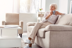 Frau mit Tasse Kaffee auf dem Sofa