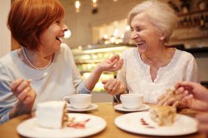 zwei lachende Frauen bei Kaffee und Kuchen