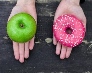 Ein Apfel und ein Donut jeweils auf einer Hand