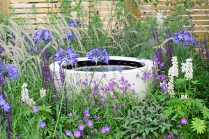 moderner Wasserbrunnen mit lila Blumen
