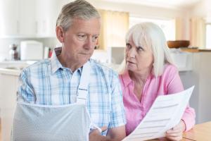 Mann mit gebrochenem Arm und Frau schauen sich Dokument an