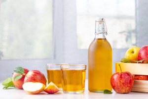 Stilleben mit Apfelessig und Äpfeln
