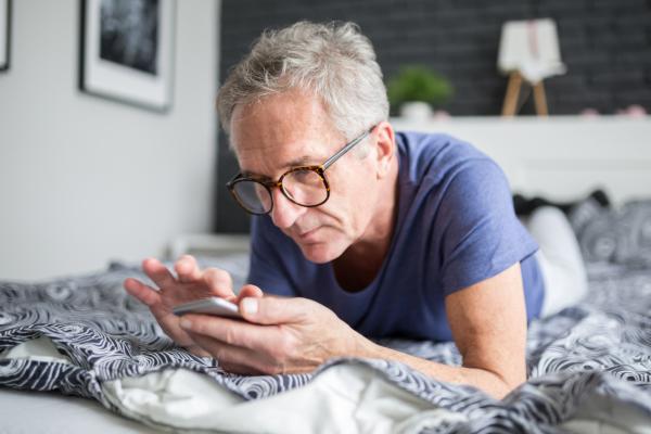 Älterer, auf dem Bett liegender Mann liest auf dem Smarthphone