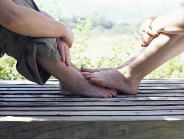 Füße eines Paars auf Holzsteg