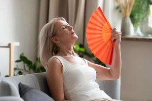 Seniorin fächert sich kühle Luft bei Hitze zu