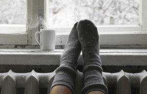 Mit warmen Socken auf Heizung und Blick aus Fenster