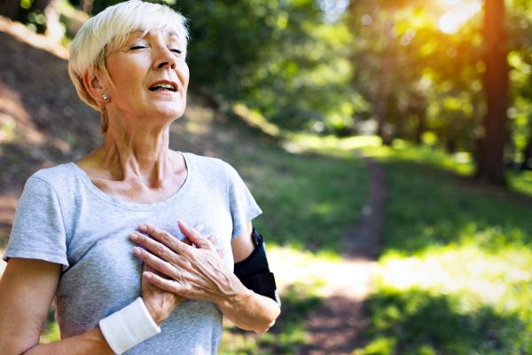 Ältere sportliche Dame, die sich an die Brust fasst