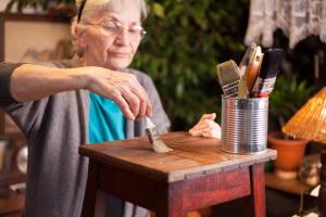 Frau streicht einen kleinen Tisch