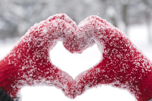 Hände mit roten, geeisten Handschuhen formen ein Herz