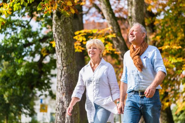 Seniorenpaar bei Spaziergang durch den Herbstwald