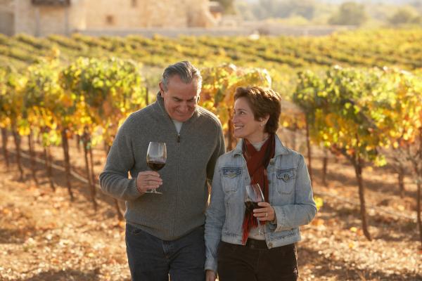 Paar mit Weingläsern in herbstlichen Weinbergen