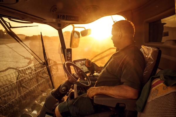Landwirt auf Mähdrescher in der Abendsonne