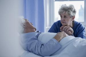 Frau steht traurig bei ihrem Mann am Bett