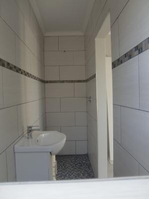 Bad mit Waschbecken in der Mitte, WC und Dusche vorne und hinten.