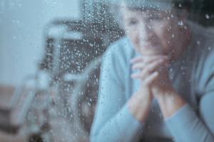Frau in Trauer hinter einem Fenster