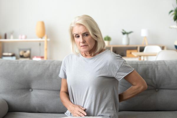 Frau, die sich besorgt den Rücken und den Bauch hält