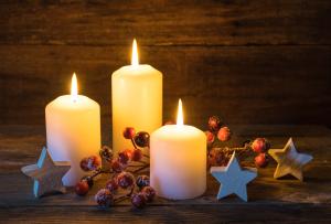 drei brennende Kerzen mit Weihnachtsdekoration