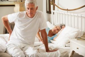 Mann mit Rückenschmerzen nach dem Aufstehen