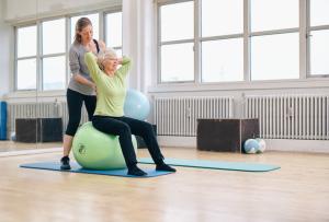 ältere Frau mit Trainerin im Fitnessstudio
