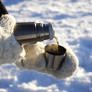 Hände in Handschuhen halten eine Thermoskanne