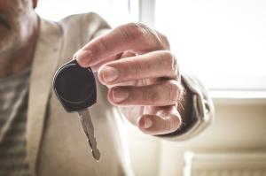 Mann überreicht Autoschlüssel