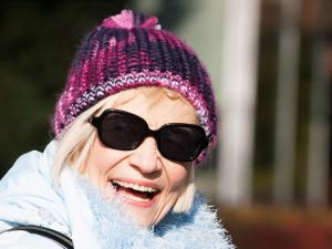 Portrait einer Seniorin mit Mütze und Sonnenbrille