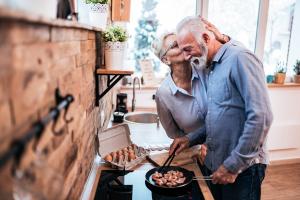 Paar beim Kochen tauscht Zärtlichkeiten aus