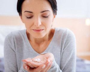 Frau blickt skeptisch auf Arznei