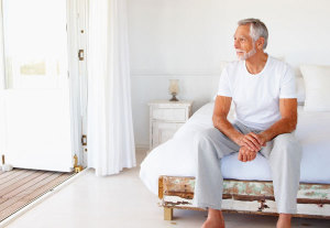 Mann sitzt auf seine Bett