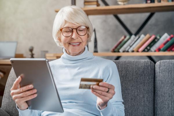 Seniorin mit Notebook und Handy