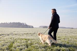 Mann geht mit Hund spazieren in Winterlandschaft