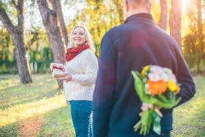 Älterer Mann versteckt Blumenstrauß hinter dem Rücken, sie mit Geschenk in der Hand