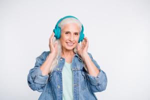 Seniorin mit grauen Haaren und türkisfarbenen Kopfhörern
