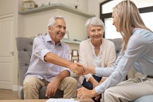 Seniorenpaar schüttelt Hand mit jüngerer Frau