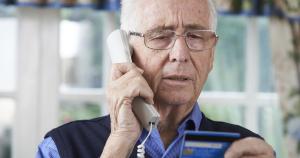 Senior telefoniert und schaut auf Kreditkarte