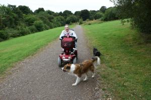 Frau mit Hund fährt Elektromobil auf Schotterweg