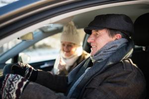 Seniorenpaar im Auto bei Winterfahrt