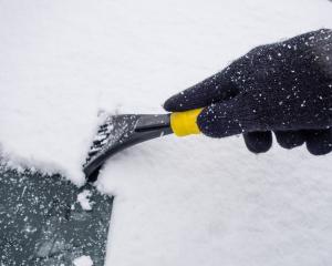 Autoscheibe wird mit Eiskratzer von Schnee befreit