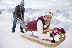 älteres Paar im Schnee, Frau liegt auf Schlitten
