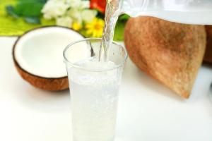Kokoswasser in einem Glas, im Hintergrund Kokosnüsse