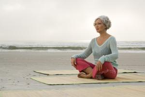 Frau sitzend auf einer Yogamatte
