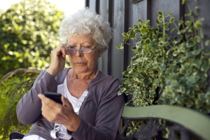 Frau schaut skeptisch aufs Telefon