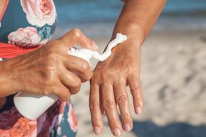 Frau schmiert sich Creme auf den Arm